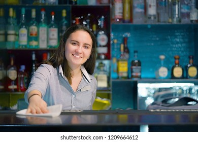 Bartender smiles, wiping the table with a rag at the hotel bar. Bartender in the workplace. Shelves with bottles of alcohol in the background. The concept of work and service.