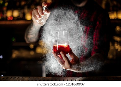 Bartender spraying on a Sazerac cocktail with orange zest on the bar counter on the blurred dark and yellow light background