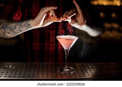 Bartender sprinkling fresh orange peel juice into a tasty Cosmopolitan cocktail on the bar counter
