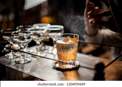 Bartender sprinkling with an orange juice from a zest to the fresh delicious alcoholic summer cocktail