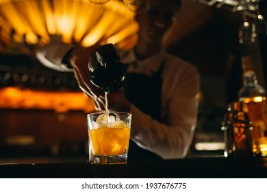 The bartender squeezes citrus juice into a cocktail