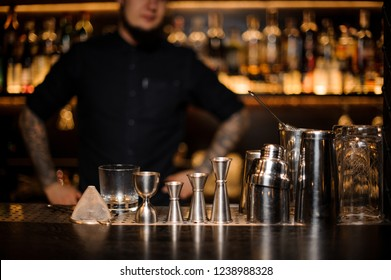 Bartender standing on the bar on the foreground of equipment such as jiggers, shakers and strainers