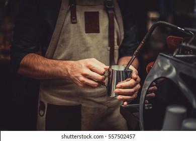 Bartender steaming milk on espresso machine in coffee shop