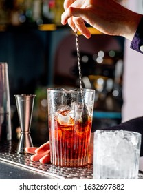 bartender stirs cocktail and ice