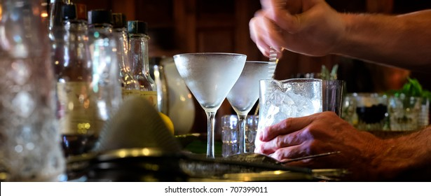 Bartender stirs a cocktail with motion blur. Selective focus on the frosty glasses. View from behind the bar.