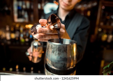The bartender strains a cocktail in a glass at a nightclub, beach, pub, restaurant