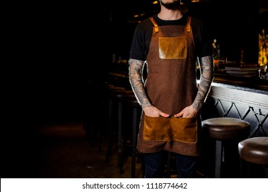 Bartender with tattoo on hand dressed in brown apron standing near the dark bar counter in night club