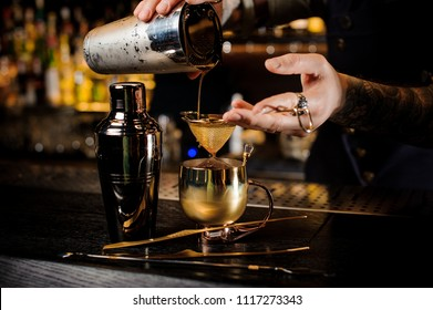 Bartender with tattoo pouring fresh and tasty summer drink from shaker into the vintage copper mug on bar counter