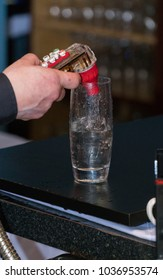 Bartender uses fountain soda gun to pour alcoholic mixed drink into tall glass with ice for thirsty customer.