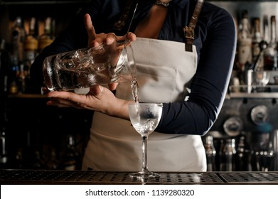Bartender in the white apron pouring an alcoholic drink from the measuring cup into the cocktail glass at the bar counter