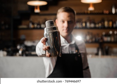 Bartender in white shirt and apron holding a shaker on the background of shelves with bottles and bar counter