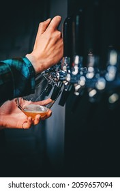 bartender woman's hand holds a glass and pours light craft beer from the tap. taproom
