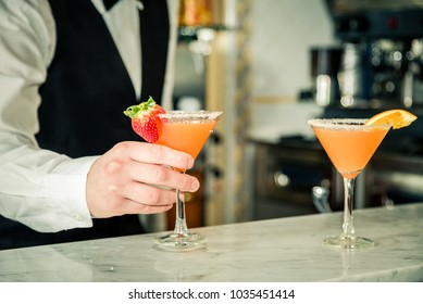 Bartender's hand serving a cocktail. Two orange cocktails with fruit slices on the bar counter in blurred background