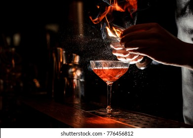 Bartender`s hands sprinkling the juice into the cocktail glass filled with alcoholic drink and making a smoky note on the dark background