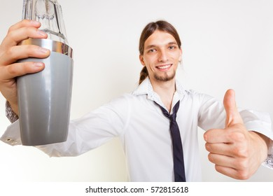 Bartending celebration party relax alcohol liquor concept. Happy bartender makes gesture. Young male holding glass shaker showing thumb up.