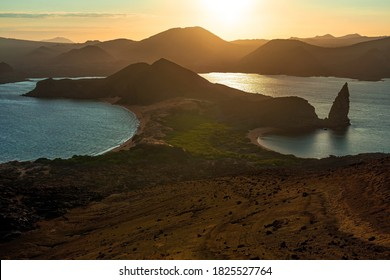 Bartolome island with Pinnacle Rock at sunset with Santiago island in the background, Galapagos national park, Ecuador.