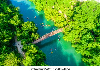 Barton Creek Bridge spanning across the cold spring fresh clear waters of Barton Creek in Austin Texas skyline cityscape aerial drone view above green landscape Barton creek flowing into town lake