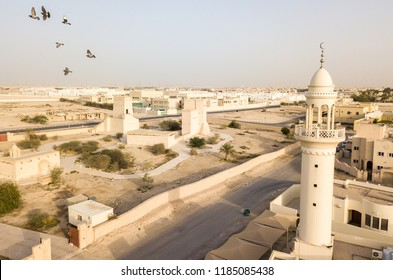 Barzan watchtowers and a mosque. Ancient Arabian fortification. Fort Towers. Aerial drone foto with birds of traditional and modern arab town of Umm Salal Mohammed, near Doha city, Qatar.