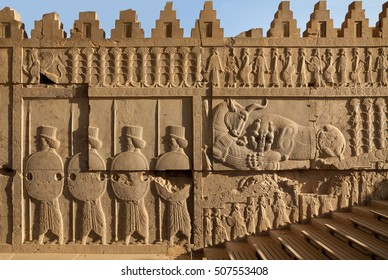 Bas relief carvings of a lion hunting a bull beside embossed soldiers on one of the staircases in Persepolis UNESCO World Heritage Site near Shiraz, belonging to Achaemenid Empire, 500 BC.
