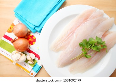 Basa fish fillets over wooden background