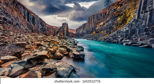 Basalt cliffs in deep canyon of mountain river. Dramatic spring view of Studlagil Canyon. Exciting morning landscape of Jokulsa A Bru river, Iceland, Europe. Beauty of nature concept background.