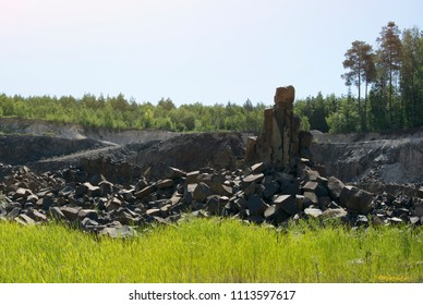 Basalt rock climbs over bright green grass under the sunny summer light on the background of the forest, basalt quarry