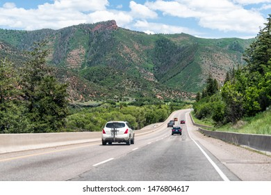 Basalt, USA - June 29, 2019: Road highway 82 to Aspen, Colorado town with cars in traffic and red mountains