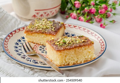 Basbousa or namoora ao revane - semolina cake with pistachios on ornament plate and white wooden background. Slise of cake.  East cuisine. Spring mood