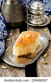Basbousa (namoora) - arabian semolina cake with almond and honey syrup in iron vintage tray on wooden background. Slice of cake