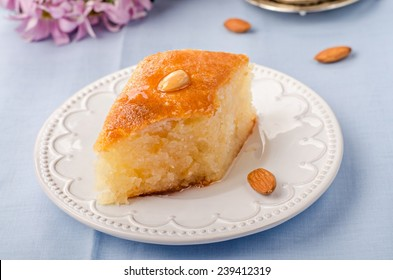 Basbousa (namoora) - arabian semolina cake with almonds and honey syrup in white plate on blue cotton background