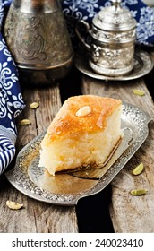 Basbousa (namoora) - arabian semolina cake with almond and honey syrup in iron vintage try on wooden background. Slice of cake