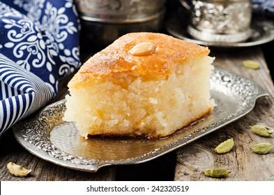 Basbousa (namoora) - arabian semolina cake with almond and honey syrup in iron tray on wooden background. Slice of cake