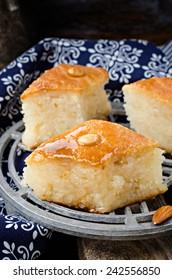 Basbousa (namoora) - arabian semolina cake with almonds and honey syrup on iron support. Slices of cake
