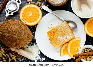 Basbousa (namoora) - arabian semolina dessert. Slice of cake and ingredients on black table top view, food composition