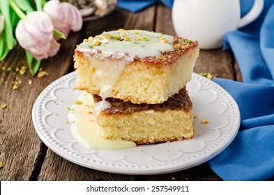 Basbousa (namoora or revane) - semolina cake with condensed milk on wooden background