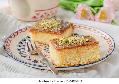 Basbousa (revane) - semolina cake with pistachios on ornament plate and white wooden background. Slise of cake.  East cuisine. Spring mood