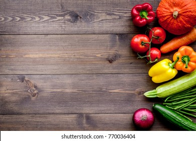 Base of healthy diet. Vegetables pumpkin, paprika, tomatoes, carrot, zucchini on dark wooden background top view copyspace