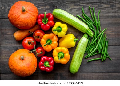 Base of healthy diet. Vegetables pumpkin, paprika, tomatoes, carrot, zucchini on dark wooden background top view