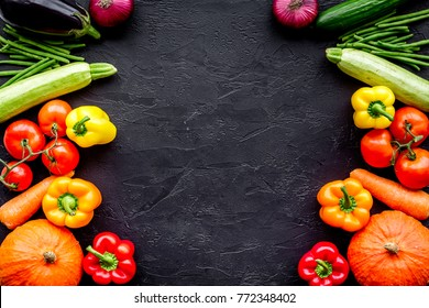 Base of healthy diet. Vegetables pumpkin, paprika, tomatoes, carrot, zucchini, eggplant on black background top view copyspace