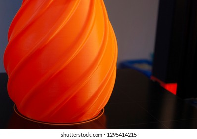 base of an orange 3d printed vase on the print bed with a dark background