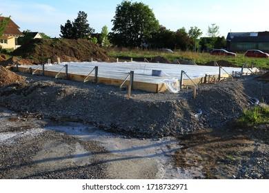 Grundplatte frisch verziert. Um den frischen Beton feucht zu halten, ist er mit Folie bedeckt. Sonnenlicht. Neu mit Formalitäten gebaut.