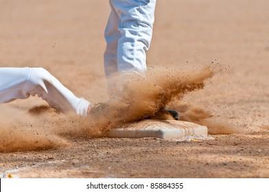 Base runner sliding into third base, close up on base