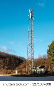 Base Transceiver Station or cell phone tower in front of blue sky with small shed in Autumn scenery