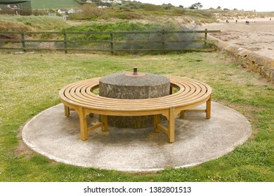The base of a World War 2 era anti-tank spigot mortar, with a modern bench around it. The original mortar trench emplacement is clearly defined by the concrete foundation