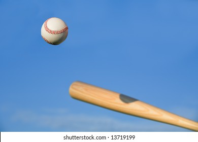 Baseball about to be struck by baseball bat with blue sky background.