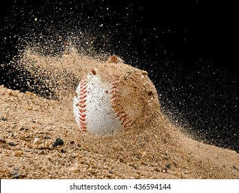 Baseball ball falling in a sand