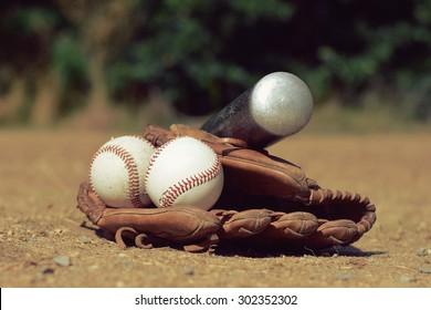 Baseball ball in leather glove with a baseball bat lying on the playground