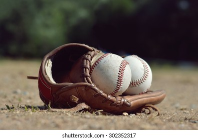 Baseball ball in leather glove lying on the playground