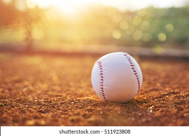 Baseball ball on pitchers mound. Baseball field at sunset