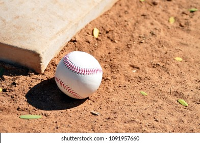 baseball and base on dirt field